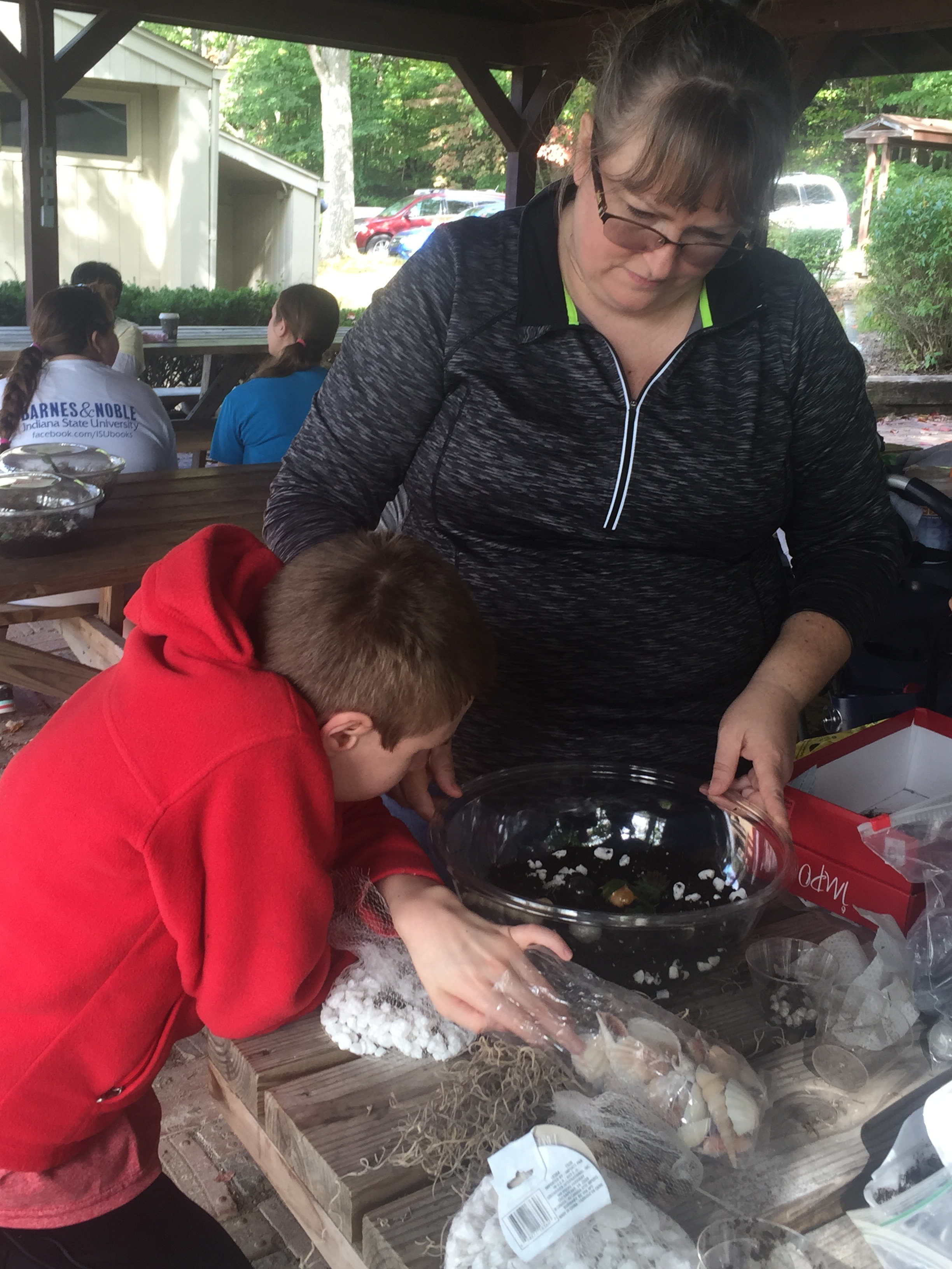 Young man in red hoodie making a planter out of a clear bowl with help from adult woman.